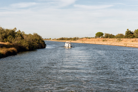 Boat cruising down a canal in the Camargue , France viewed from behind as it leaves a wide wake in the tranquil water