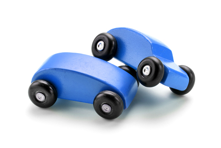 pileup: Wooden blue toy car crash isolated against white background