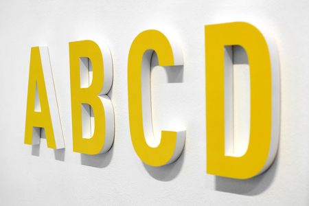 ABCD yellow alphabet letters mounted on a white wall with shadow viewed at an oblique angle with D in the foreground
