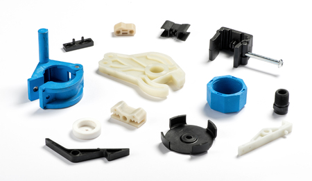 Many different injection plastic parts of white, blue and black colour spread on white background Stockfoto