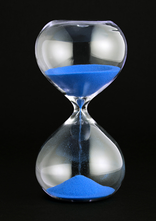 Close-up studio shot of a transparent hourglass with blue sand pouring as concept for time and countdown against black background for copy space