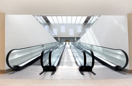 Two empty escalators, one ascending and one descending, side by side in a brightly lit commercial building