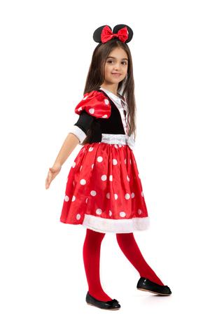 Pretty graceful little ballet dancer in a cute red costume with a gathered polka dot skirt and red bow in her hair, side pose looking at the camera over white