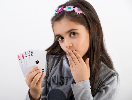 Secretive pretty young girl showing her winning poker hand with four aces and a king to the camera with a coy expression, head and shoulders over white Stock Photo