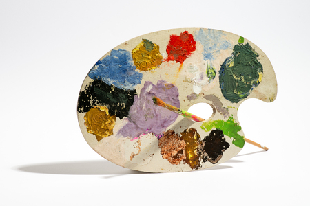 Painting palette with brush and colorful paints against white background Stock Photo