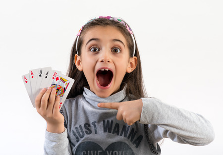 Excited little girl pointing to a winning poker hand with four aces and a king with wide eyes and her mouth open, over white