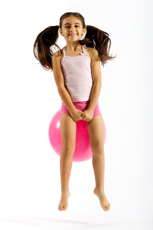 Vivacious little girl on a bouncing ball playing happily with a beaming smile and her pigtails flying up in the air as she bounces along, isolated on white