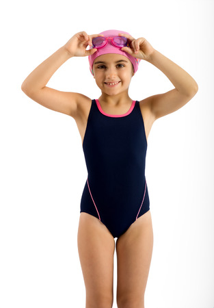 Close up Pretty Young Girl in Swimming Fashion Outfit with Pink Head Cap and Goggles, Smiling at the Camera. Isolated on White Background. Stock Photo