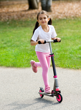 Cute young girl in pink with her brown hair in pigtails playing on a push scooter outdoors on a road having fun and smiling