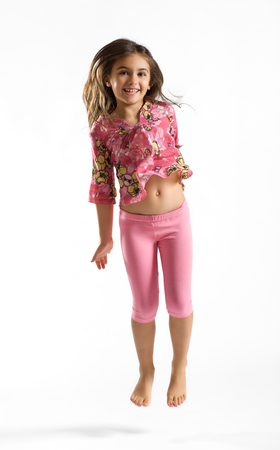 Cute pretty young girl in a stylish pink outfit with a bare tummy and feet smiling happily at the camera, full length portrait on white