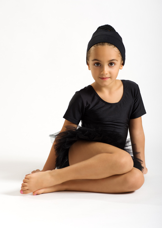 Small pretty young ballerina sitting barefoot on the ground in her bare feet and black tutu with her hair tied up in a bun looking at the camera with a quiet smile
