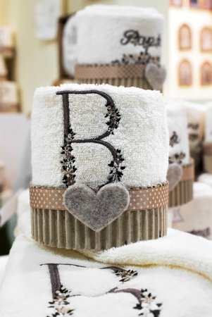 Decorative embroidery on towelling fabric with the letter B with a pleated border and heart below on display in a store Stock Photo