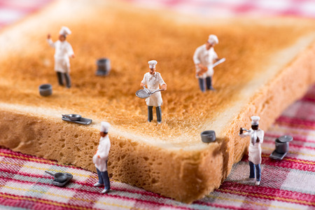 Group of miniature cooks or chefs on a slice of white toast in a concept of teamwork in preparing food and catering