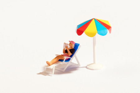 Miniature person reading a book relaxing on a recliner chair sunbathing in the shade under a colorful beach umbrella over white with copy space