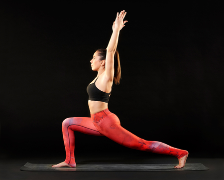 Sporty young woman practicing yoga doing the crescent lunge pose with her arms extended above her head over a black background with copy space Stock Photo