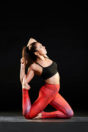 Fit young woman performing a mermaid pose variation during a yoga workout in a close up side view over black with copy space in a healthy lifestyle concpet