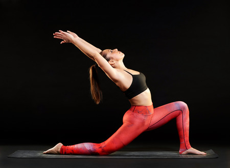 Fit woman demonstrating a low lunge pose in yoga stretching and arching back to tone her muscles, side view over a black background Stock Photo