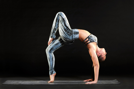 Fit healthy woman doing a one legged wheel pose while working out on a yoga mat arching her back gracefully with one leg raised over a black background