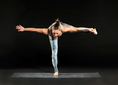 Woman doing balancing exercises during a yoga workout adopting a hand to big toe standing balance pose on one leg with outstretched arms and leg over black Stock Photo