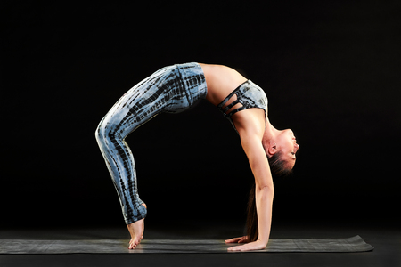 Supple woman demonstrating the wheel pose in yoga balancing while arching her back with feet and hands on the mat over black in a side view