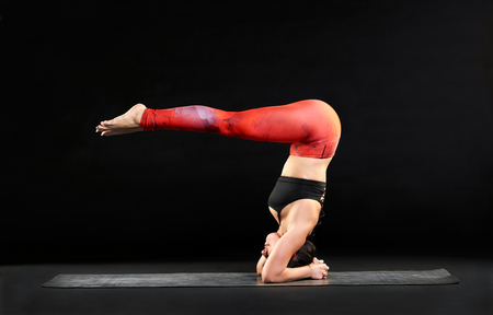 Fit muscular woman doing a headstand with pike legs balancing on her forearms and head on a yoga mat with body extended at right angles over a black background Stock Photo