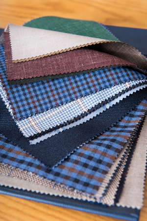 Close up view of fabrics samples on table in tailor workshop