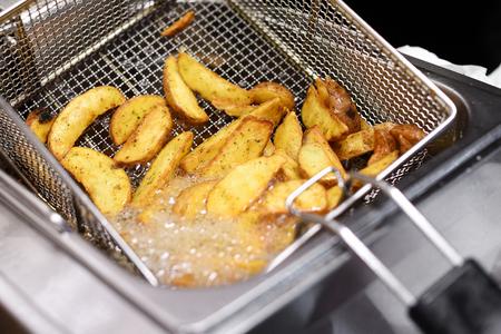 Würzige Kartoffelchips oder Keile, die in einer Fritteuse in einem Abschluss herauf Ansicht des heißen sprudelnden Öl- und Drahtmetallkorbes kochen