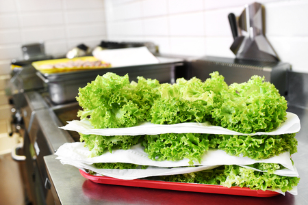 Stacked fresh frilly lettuce leaves for use as salad greens in a restaurant kitchen