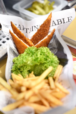 Portions of crumbed fried fish served with potato chips and fresh frilly green lettuce on newspaper in a restaurant or fisheries