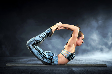 Athletic woman demonstrating the bow pose in yoga in a close up side view over a black background with smoke  Stock Photo