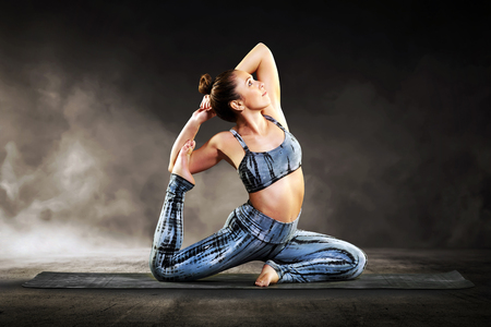 Young woman doing a pigeon pose during a yoga workout on a mat in a close up side view in a health and fitness concept