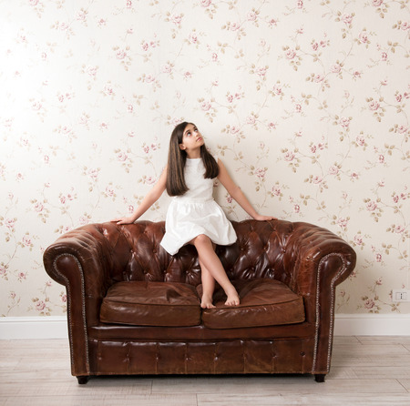 Thoughtful dreamy girl wearing white dress sitting on leather vintage sofa