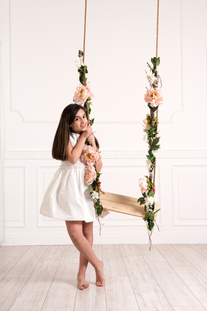 Pretty barefoot young girl posing with a flower decorated swing indoors in a large bright airy room at home smiling at the camera