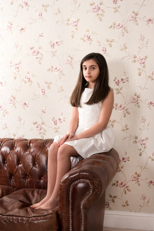 Portrait of young girl in white dress calmly sitting on top of leather sofa in the room