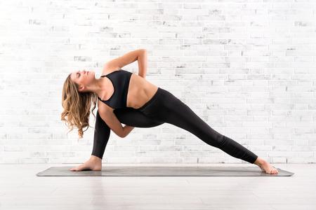 Young flexible woman performing utthita parsvakonasana full bind yoga pose