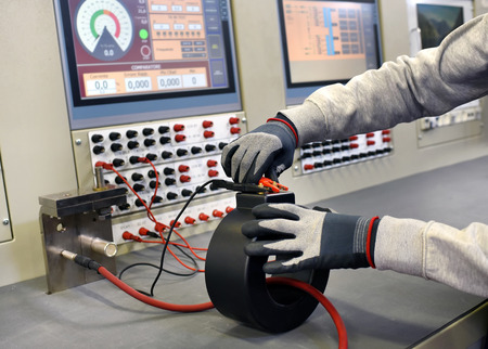 Workman in a factory testing a new transformer attaching electric cables to measure the input and output voltage on a digital screen in a close up view of his gloved hands