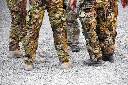 Group of soldiers wearing camouflage fatigues in a low angle view of their legs on gravel