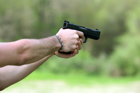 Man bare hands in close-up shooting with black handgun standing outdoors, viewed from the side