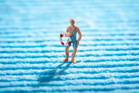 Miniature lifeguard carrying a life ring or preserver as he crosses a blue ridged textile conceptual of the sea