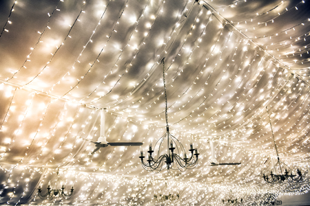 Twinkling party lights and chandeliers decorating a marquis ceiling in a wedding tent or at an event in a full frame background