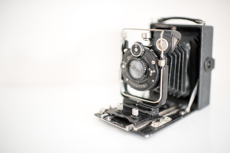 Old vintage black box camera for photography opened to display the bellows and lens over a white background with copy space