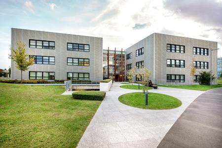 Jardin paysager en face d'un complexe de bâtiments modernes avec deux ailes symétriques autour d'une section centrale en verre Banque d'images - 109714615