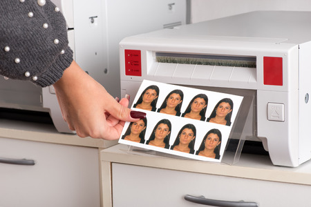 Set of just printed passport photos of a young woman exiting the printer with the hand of a woman reaching for the sheet in a close up view Archivio Fotografico