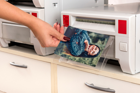 Woman taking a colored photographic print of a smiling pretty woman from a printer in a close up view of her hand and the machine