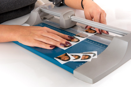 Woman cutting and sizing passport photos in a photographic studio on a small portable guillotine in a close up view of her hands