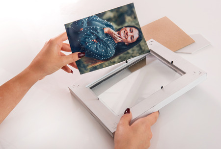 Woman placing a colored photo of a smiling lady in a simple white wooden frame in a close up view of her hands