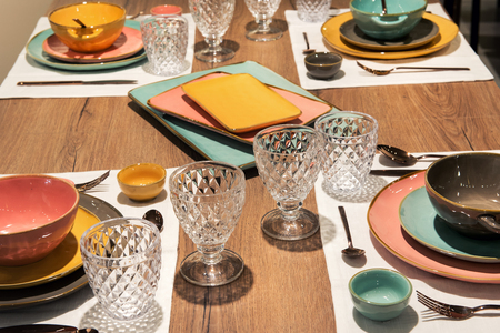 Mise en place dinner table with elegant colorful ceramic dinnerware and cut glass goblets for a formal dinner or catered event Reklamní fotografie