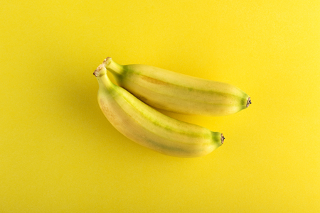 Two small whole bananas viewed from above isolated on yellow background