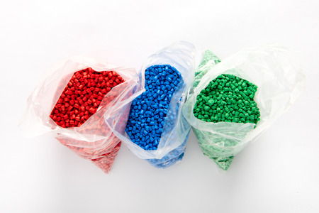 Bags of colorful plastic granules of red, blue and green colors. Viewed from above on white background with shadow Stock Photo
