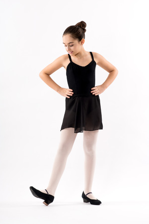 Young character ballerina in a black outfit wearing low healed court shoes standing with hands on hips looking down at her foot with a smile isolated on white Stock fotó